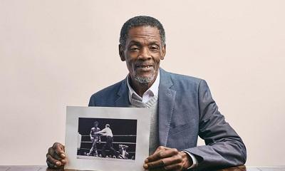 Vernon Vanriel holding a photo of himself boxing