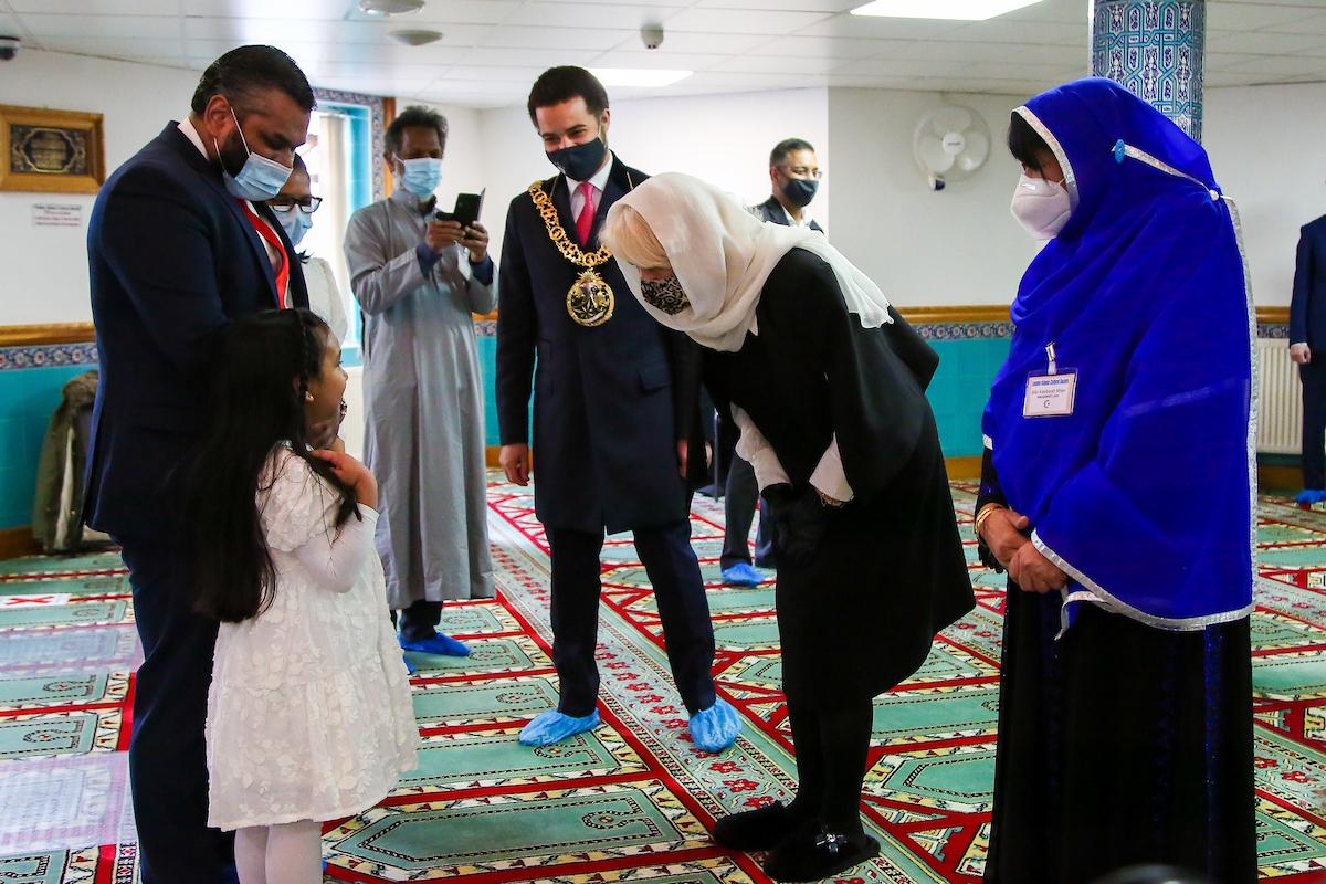 Her Royal Highness the Duchess of Cornwall chats to a young girl during her visit to Wightman Road Mosque.