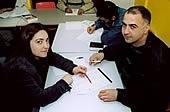 Two adults writing in a classroom